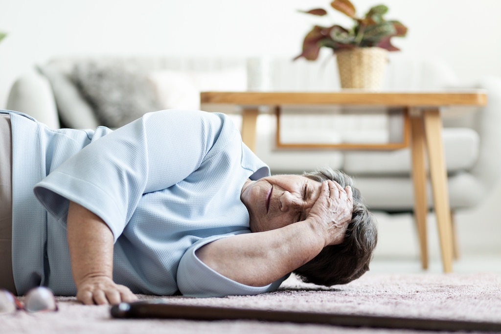 Senior woman with a headache after falling down at home